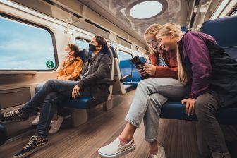 Reizigers in trein met mondkapje (bron: OV-NL)